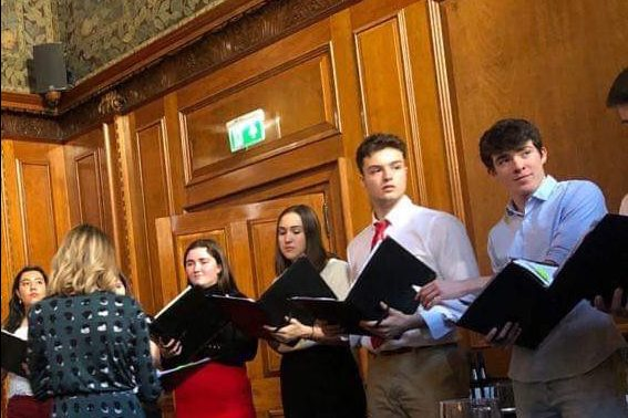 Members of the Chamber Choir prepare to sing at The Ned Hotel. Left to right: Cate Parkinson ('21), Claire Heskett ('22), Darby Craig ('21), Eli Anderson ('22).