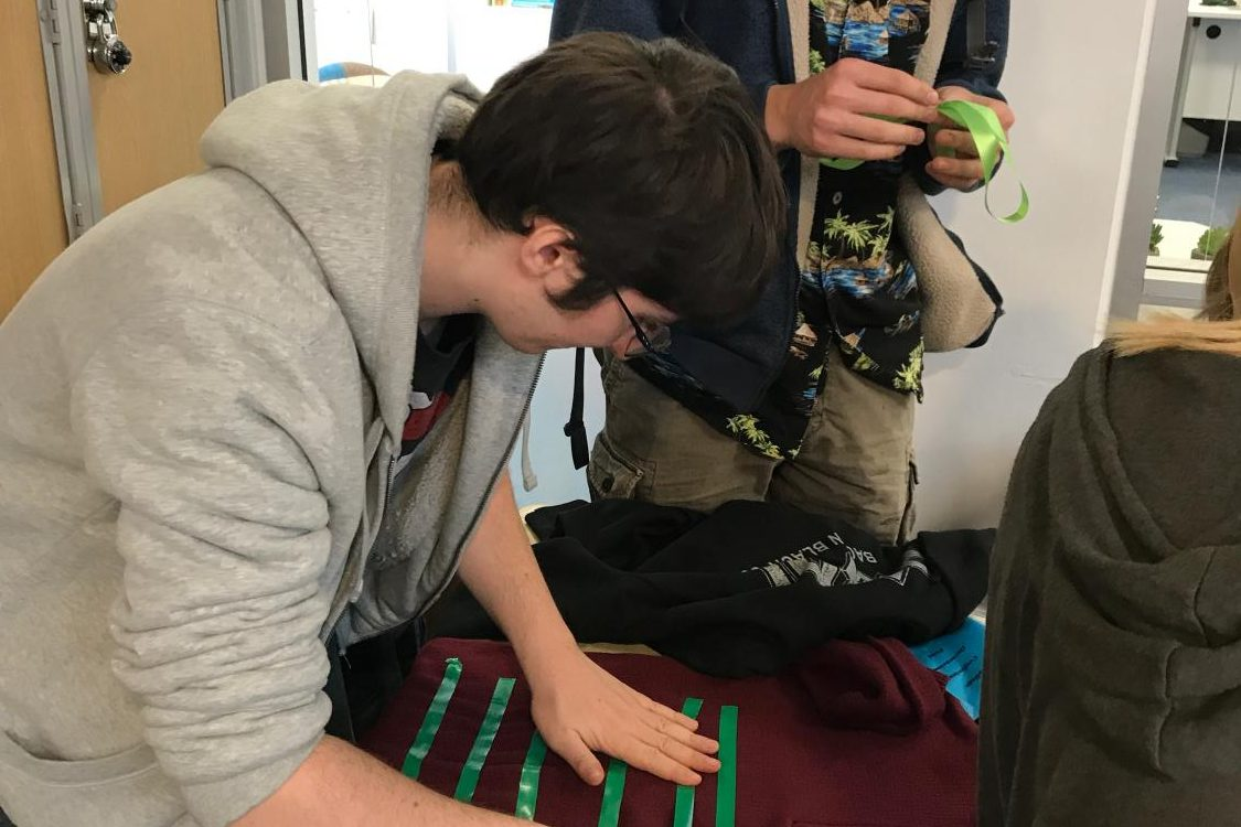Tomas Belinky ('20) makes his own ugly sweater. The lunch-time event, hosted by the Sustainability Council, offered a chance for students to get in the holiday spirit while combatting fast fashion and waste.