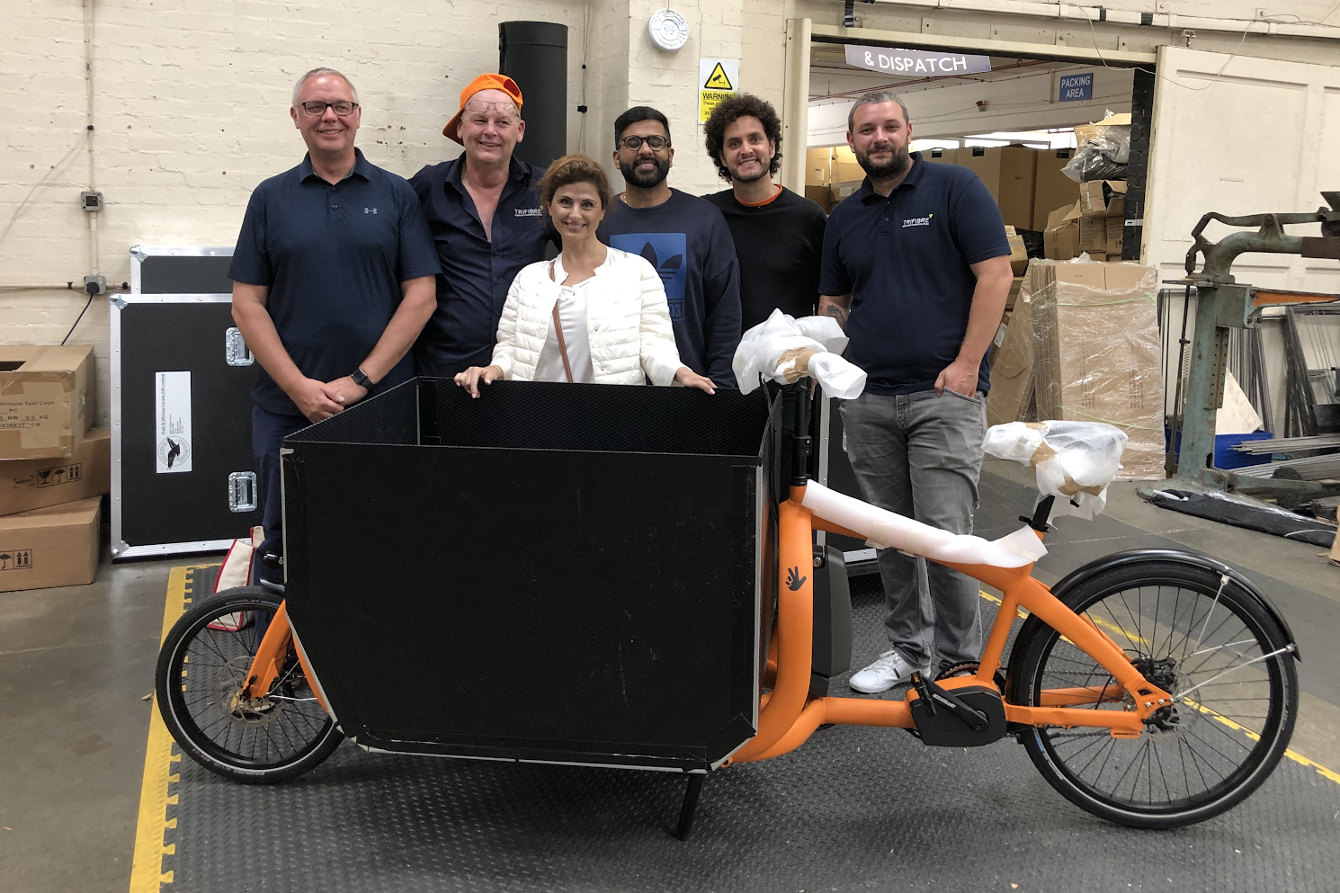 Fareh Asemi (P'11) poses with the assembly team of a prototype of the ecofleet bike. ecofleet is a new carbon neutral delivery company based in London.