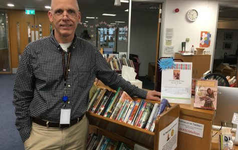 Library Administrative Assistant Steve Reed stands with the bookcase of all the Newbery Medal award winners. Reed has taken on the challenge to read all the winners since the founding of the medal in 1922.