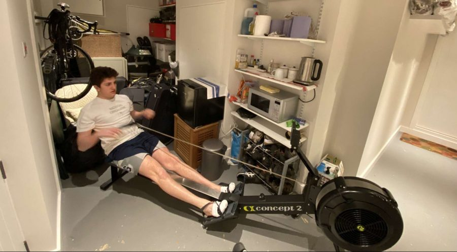 Performance crew team member Leyth Sousou ('22) trains on an erg at home. Crew had many races scheduled for the spring season, but they were canceled. Sousou has been able to train six times a week on the erg, but finds it hard be motivated to train without the other members of the team.