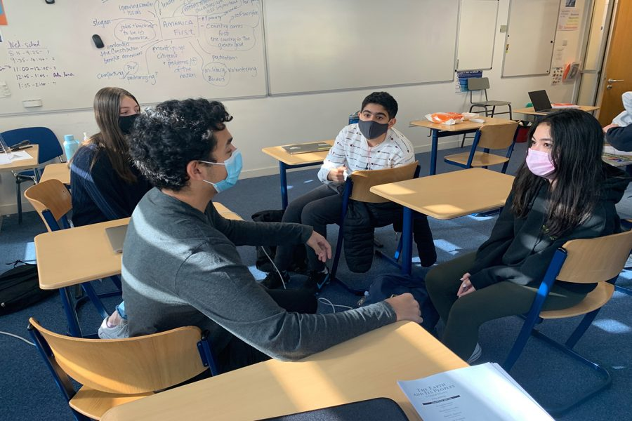 Samih Sawiris ('23), Emma Lucas ('23), Ana Costa ('23) and Ruhan Basin ('23)  discuss and debate the upcoming election in their World Civilizations II class.Social Studies classes have attempted to weave the election into curriculums and lessons to keep students informed.