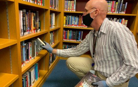 With gloves on, Library Administrative Assistant Steve Reed retrieves a book from the shelves of the Mellon Library. The process for borrowing books follows a new quarantine protocol to prevent the spread of COVID-19.