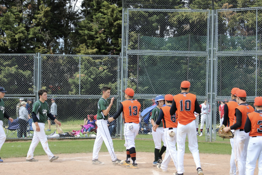 The varsity baseball team shakes hands with ACS Cobham after an ISSTs game in 2019. ASL hosted softball and baseball ISSTs at Canons Park, and both teams won gold.