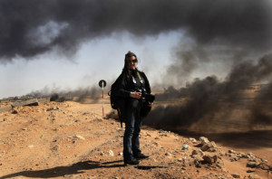 Photographer Lynsey Addario stands near the frontline during a pause in the fighting while covering the popular uprising for The New York Times, March 11, 2011 in Ras Lanuf, Libya.