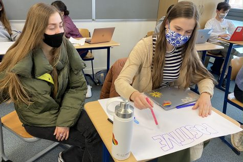 "Katie Brosnan ('21) and Cece Muecke ('21) create a poster highlighting female athlete role models. Their poster was part of a mixed media project worked on by participants of the ""You Play Like a Girl"" workshop, which focused on bringing attention to gender inequalities in sports."