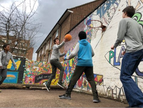 Ben Perrin ('19) plays basketball with kids at the St. John's Wood Adventure Playground pre-pandemic. The community partnership, now at the site called the St. John's Wood Adventure Playhub, is the first to return in person, running Monday through Friday.