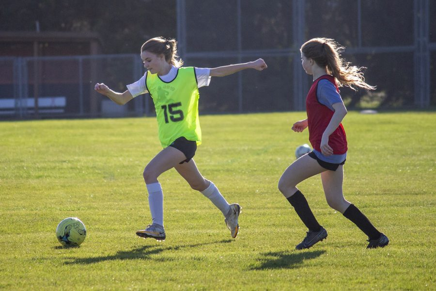 Olivia Lang ('22) dribbles away from Casey Johnson ('23) March 29 and looks to pass to a teammate.