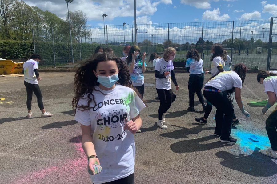 """Reese Laurienti ('23) holds Holi powder used to decorate T-shirts worn by Concert Choir members while recording """"Balleilakka"""" at Canons Park May 4. The choir's spring concert went live June 6, showcasing """"Balleilakka"""" alongside other parts of their repertoire."""