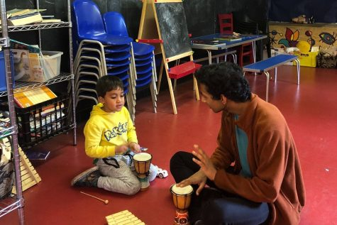 Rohan Prasad ('18) plays with a child at St. Johns Wood Adventure Playground in March 2018. This spring, the same community partnership resumed in person.