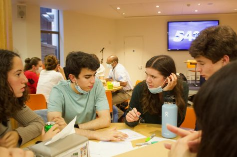 """Adnan Bseisu ('22) and Lily Bernhard ('22), members of the """"Amazing Avocados"""" team, discuss potential answers to a trivia question during the third round of Quiz Night. """"Amazing Avocados"""" placed second overall after points accumulated by each team were tallied."""