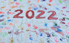 """The completed Grade 12 banner lies on the ground in the Coreen Hester Courtyard Aug. 31. Members of the grade collaborated throughout the day to decorate the banner, which Saskia Whitmoyer ('22) described as """"a really great grade bonding activity."""""""