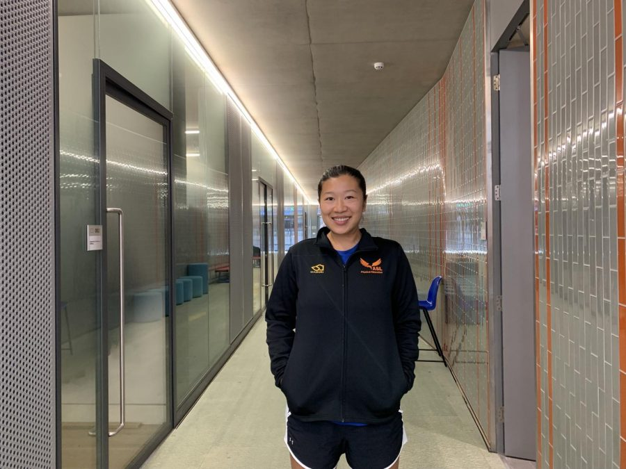 MS/HS PE Teacher Bonnie Lam smiles in the hallway near the pool. Lam found a passion for teaching PE after growing up playing sports and seeing how the skills she learned could be applied to other facets of life.